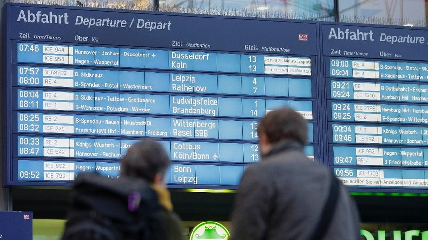 Travellers stay in front of an information board at the main railway station in Berlin, Germany, Thursday, Nov. 6, 2014. A union representing German train drivers on Tuesday called its members out on a four-day strike, escalating a bitter contract dispute with the national railway operator just as the government considers how to rein in the power of small unions. The GDL union said the strike will run from early Thursday morning until Monday, Nov. 10. It follows a series of shorter strikes, including a two-day walkout last month. (AP Photo/Michael Sohn)