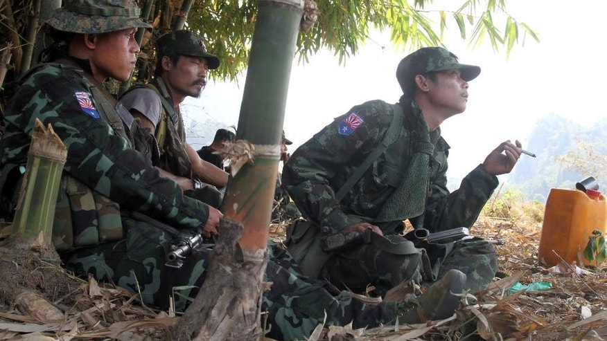In this Feb. 12, 2013 photo, soldiers of Karen National Union (KNU) take a rest as they patrol in Hpa-an village, Karen State, Myanmar.  Military activities carried out by Myanmar's powerful minister of home affairs Ko Ko when the country was under dictatorship could constitute war crimes, a new study charges, saying there is evidence that he and two other generals were responsible for the executions, torture and enslavement of civilians by troops during a large-scale offensive against ethnic rebels. (AP Photo)