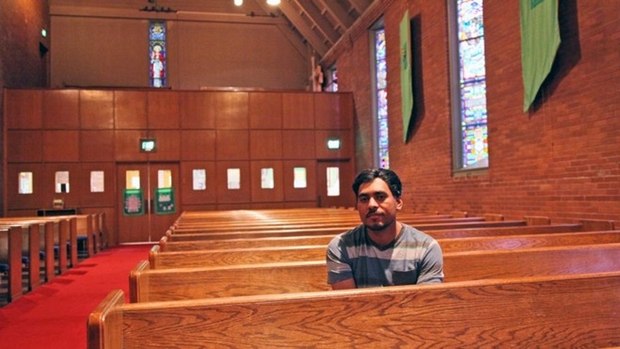 Francisco Aguirre - a community activist who first came to the U.S. from El Salvador two decades ago - poses for a photo on Sept. 24, 2014, in the church where he has taken refuge nearly a week ago to avoid deportation. Aguirre, who has two U.S. citizen children, is facing removal to his native country due to an old drug trafficking conviction and a previous deportation. (AP Photo/Gosia Wozniacka)