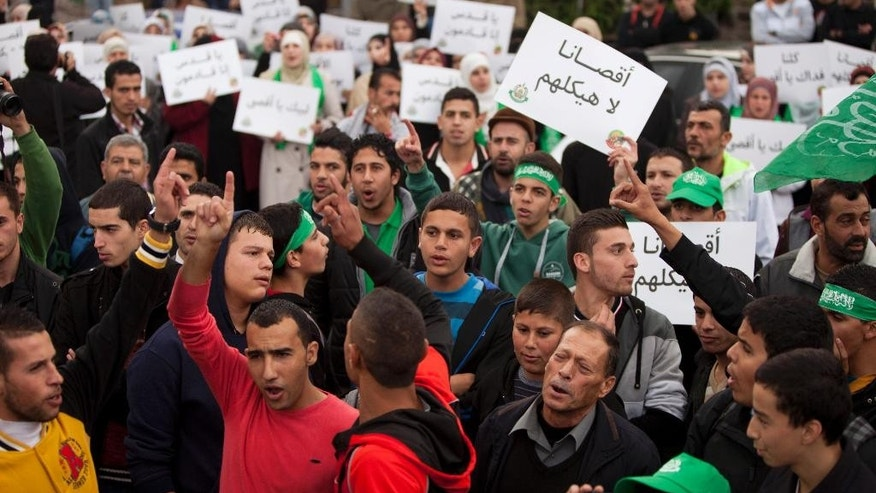 "Palestinian supporters of the Islamist movement Hamas shout slogans and hold  pears with a slogan written in Arabic, ""our Al-Aqsa is not their temple,"" during a protest against Israeli restrictions at the Al-Aqsa Mosque, in the West Bank City of Ramallah, Friday, Oct. 17, 2014. (AP Photo/Majdi Mohammed)"