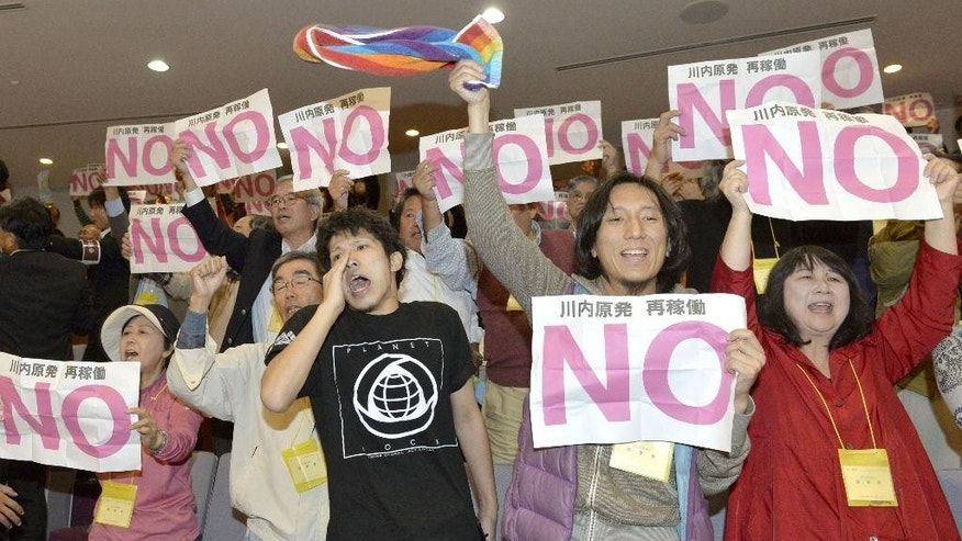 "Flashing ""No"" signs, anti-nuclear citizens shout their opposition at the gallery as the prefectural assembly adopted a petition that agrees to resume the Sendai Nuclear Power Station, in Kagoshima, Kagoshima Pref., southern Japan Friday, Nov. 7, 2014. Kagoshima Prefectural governor has given final approval to restart the nuclear power plant in Satsumasendai, the first to resume operations in the country under new safety rules imposed in the wake of the 2011 Fukushima Dai-ichi meltdowns caused by a tsunami. Kagoshima Gov. Yuichiro Ito said restarting the two reactors would go ahead even though some local residents have concerns. (AP Photo/Kyodo News) JAPAN OUT, CREDIT MANDATORY"