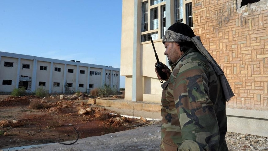 In this Monday, Nov. 3, 2014 photo, A Libyan military soldier talks on a walkie-talkie outside an empty damaged building that was used by Islamic militias during heavy clashes in Benghazi, Libya. Clashes in Benghazi have killed at least 210 people since government troops backed by armed civilians started a campaign in mid-October to retake the city from Islamist militias. (AP Photo/Mohammed El-Sheikhy)
