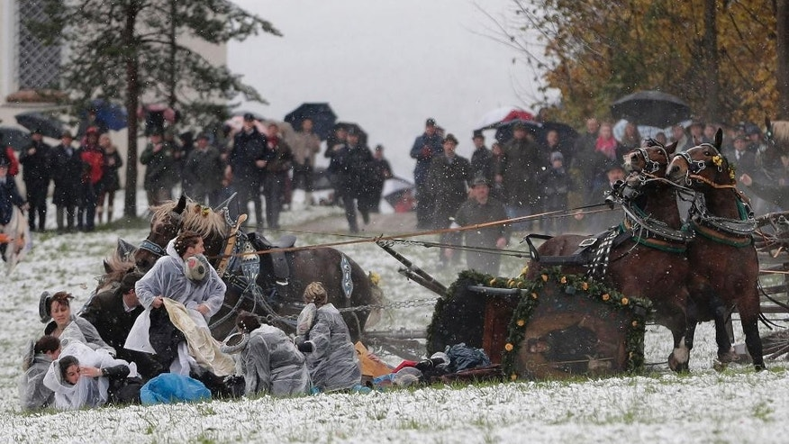 Women fall out of an overturned carriage after the horses bolted during the traditional Leonhardi pilgrimage in Bad Toelz, southern Germany, Thursday, Nov. 6, 2014. Several people were injured in the annual pilgrimage honoring St. Leonhard, patron saint of the highland farmers for horses and livestock. (AP Photo/Matthias Schrader)