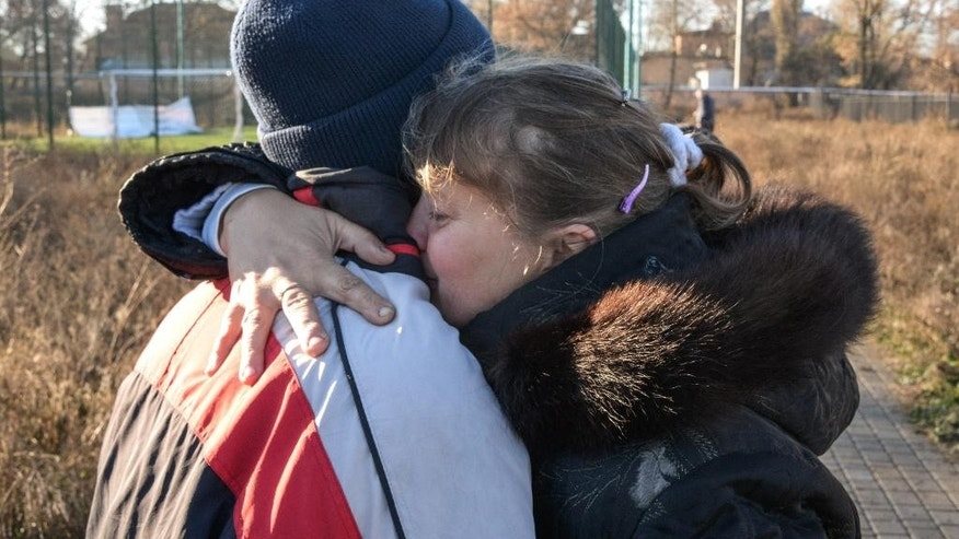 Unidentified parents of the killed and injured children embrace at the place of the tragedy at a football pitch in Donetsk, Eastern Ukraine on Thursday, Nov. 6, 2014, where shelling took place Wednesday. Two bloodied coats lay on the school pitch early Thursday morning, a day after an artillery strike killed two teenagers and injured four more as they were playing football. The attack on the high school is just one example of the blatant violations of the September cease-fire between the rebels and the Ukrainian government which have become daily routine in the past weeks. (AP Photo/ Mstyslav Chernov)
