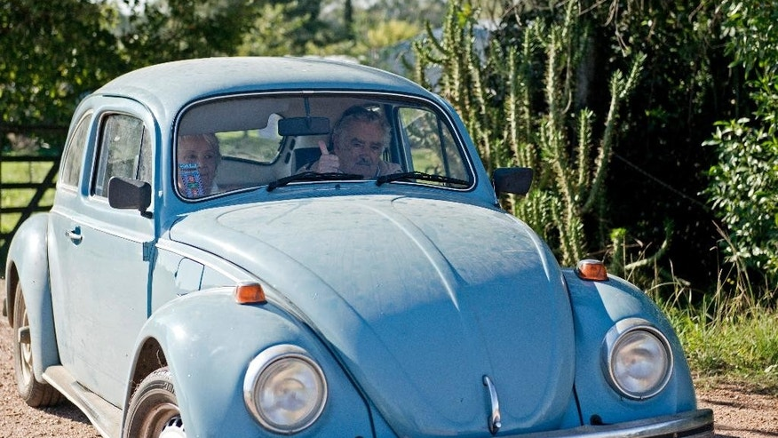 FILE - In this May 2, 2014 file photo, Uruguay's President Jose Mujica flashes a thumbs up as he and his wife, Sen. Lucia Topolansky, ride away from their home after giving an interview, on the outskirts of Montevideo, Uruguay. Mujica confirmed Thursday, Nov. 6, 2014, that he has received from an Arab shiek, a one million dollar offer for his 1987 sky blue Volkswagen Beetle. (AP Photo/Matilde Campodonico)