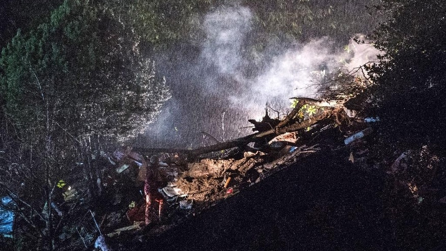 Rescue workers search in the rubble of a house that was destroyed in a landslide in Bombinasco, southern Switzerland, Wednesday evening, Nov. 5, 2014. A woman and her three-years-old child were found dead later in the building. (AP Photo/Keystone, TI-PRESS/Gabriele Putzu)