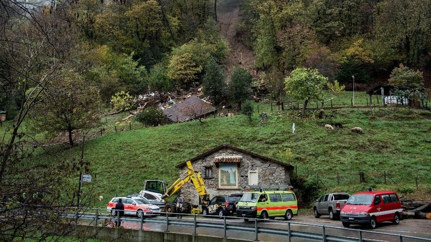 Rescue workers and police stand near the area where  a house was destroyed in a landslide. top,  in Bombinasco, southern Switzerland,Thursday  Nov 6, 2014. A woman and her three-years-old child were found dead in the building. (AP Photo/Keystone, TI-PRESS/Gabriele Putzu)