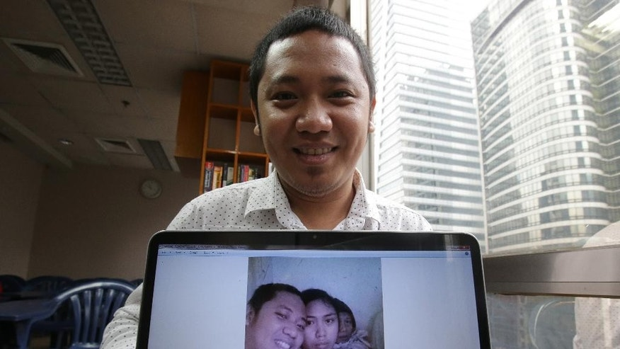 In this Oct. 14, 2014 photo, David Saavedra shows a group selfie photo with his younger sister Veronica, center, and mother at his office at the financial district of Makati, south of Manila, Philippines. The photo was taken at the second floor of their house during the height of Typhoon Haiyan in Tanauan, Leyte province, central Philippines on Nov. 8, 2013. The picture was intended to go on top of David's coffin, but instead it is a reminder of the family's immense luck, and of the obligation they feel to help neighbors who weren't nearly as fortunate when the massive typhoon hit that day. (AP Photo/Aaron Favila)
