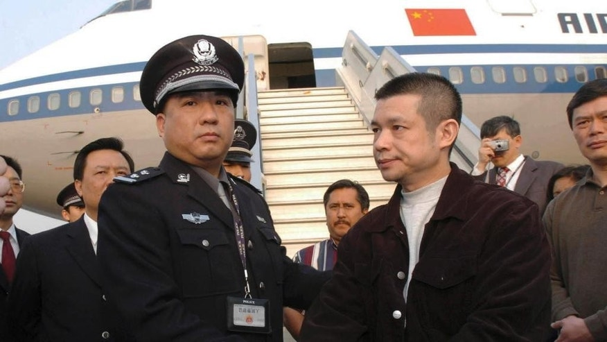 "FILE - In this April 16, 2004 file photo released by China's Xinhua News Agency, Yu Zhendong, right, a criminal suspect accused of embezzling $485 million from a Chinese state-owned bank, is arrested by Chinese police after he was returned by U.S. authorities under  a promise he won't be executed, at the International Airport in Beijing, China. China's graft busters want foreign help in their ""fox hunt"" for corrupt officials who have fled the country and stashed their ill-gotten loot abroad, but misgivings about Chinese justice may deter the U.S. and other nations from wholeheartedly joining the chase. When leaders of Asia Pacific countries meet on Nov. 10-11, 2014 in Beijing, they are expected to endorse a network for member nations to share information on corruption cases and help recover assets that have been moved across borders illegally. (AP Photo/Xinhua, Yuan Man, File) NO SALES"