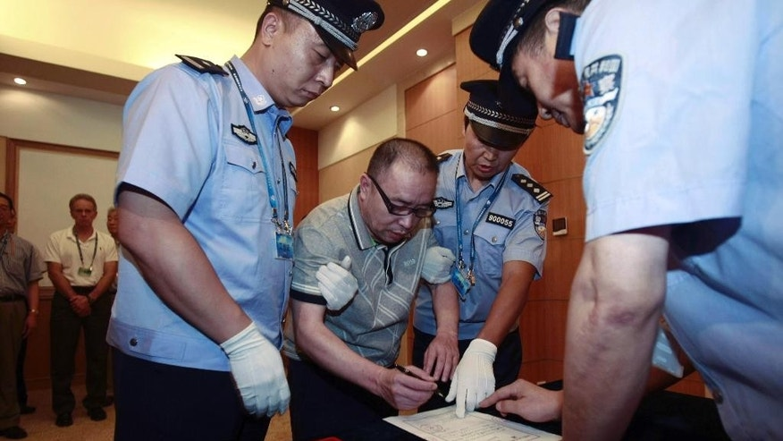 """FILE - In this July 23, 2011 file photo released by China's Xinhua news agency, Lai Changxing, center, signs a warrant issued for his arrest as he arrives at the Beijing Capital International Airport in Beijing. China's graft busters want foreign help in their """"fox hunt"""" for corrupt officials who have fled the country and stashed their ill-gotten loot abroad, but misgivings about Chinese justice may deter the U.S. and other nations from wholeheartedly joining the chase. When leaders of Asia Pacific countries meet on Nov. 10-11, 2014 in Beijing, they are expected to endorse a network for member nations to share information on corruption cases and help recover assets that have been moved across borders illegally. (AP Photo/Xinhua, Zhang Jianxin, File) NO SALES"""