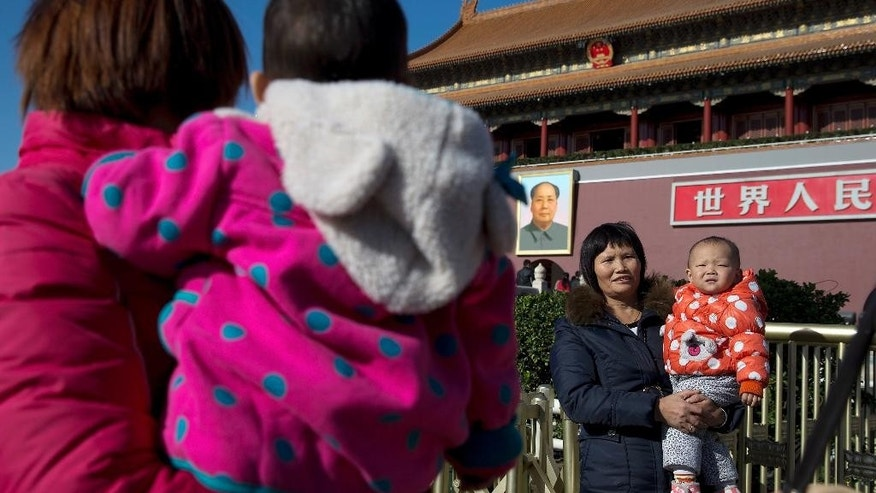 FILE - In this Nov. 16, 2013 file photo, women cuddle their child at Tiananmen Gate in Beijing, China. Despite earlier estimates that new exemptions to China's one-child policy would add up to 2 million extra births per year, only 700,000 newly qualified couples applied to have a second child this year, a Chinese official said. (AP Photo/Andy Wong, File)