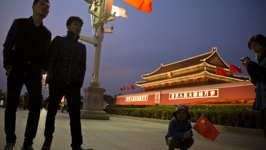 A Chinese child holds a Chinese national flag near Tiananmen Gate in Beijing, China, Friday, Nov. 7, 2014. Despite earlier estimates that new exemptions to China's one-child policy would add up to 2 million extra births per year, only 700,000 newly qualified couples applied to have a second child this year, a Chinese official said this week. (AP Photo/Ng Han Guan)