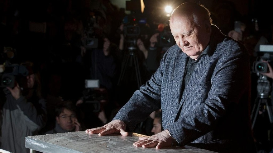 Former Soviet Leader, Mikhail Gorbachev, presses his hands in concrete attached to a piece of the Berlin wall during a reception at the Checkpoint Charlie in Berlin, Germany, Friday, Nov. 7, 2014 where the 25th anniversary of the fall of the wall is marked with numerous events on the weekend. (AP Photo/Michael Sohn)