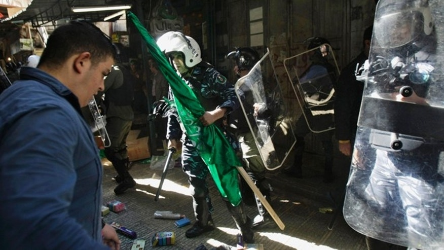 Nov. 7, 2014: Palestinian security forces take off a Hamas flag from the demonstrators during a protest against Israeli restrictions at Jerusalem's Al Aqsa Mosque, in the West Bank City of Nablus.