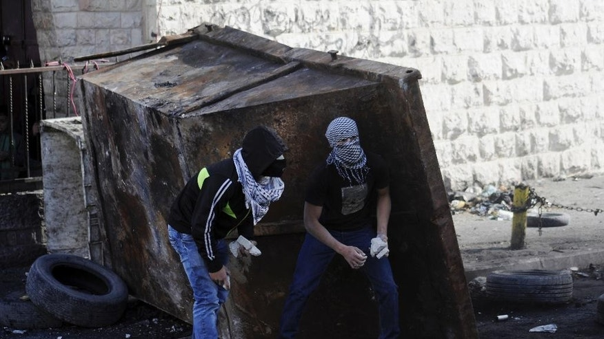 Palestinians hold stones during clashes with Israeli border police, as Israeli police limited the access to Al-Aqsa Mosque in Jerusalem on Friday, Nov. 7, 2014. Tensions have been rising in recent weeks over the Jerusalem shrine, known to Muslims as Haram al-Sharif, or Noble Sanctuary, and to Jews as the Temple Mount. (AP Photo/Mahmoud Illean)