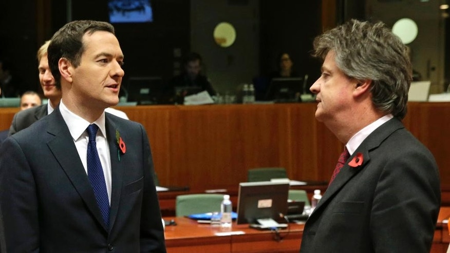 British Chancellor of the Exchequer George Osborne, left, talks with European Commissioner for Financial Stability and Financial Services Jonathan Hill, during the EU Finance Ministers meeting, at the European Council building in Brussels, Friday, Nov. 7, 2014. EU finance ministers were preparing Friday to hunt for a compromise in a row between Britain and Brussels over budget contributions, with billions of euros at stake. (AP Photo/Yves Logghe)