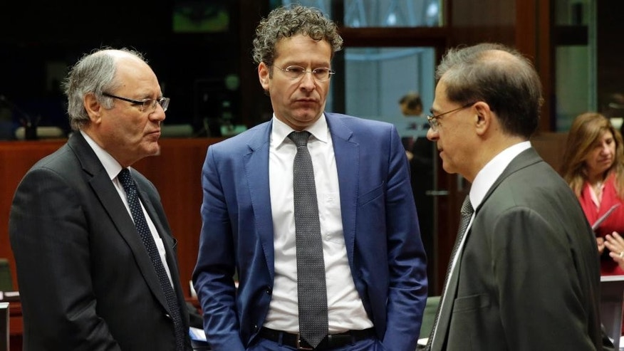 Maltese Finance Minister Edward Scicluna, left, talks with Dutch Finance Minister Jeroen Dijsselbloem, center, and Greek Finance Minister Gikas Chardouvelis, during the EU Finance Ministers meeting, at the European Council building in Brussels, Friday, Nov. 7, 2014. EU finance ministers were preparing Friday to hunt for a compromise in a row between Britain and Brussels over budget contributions, with billions of euros at stake. (AP Photo/Yves Logghe)