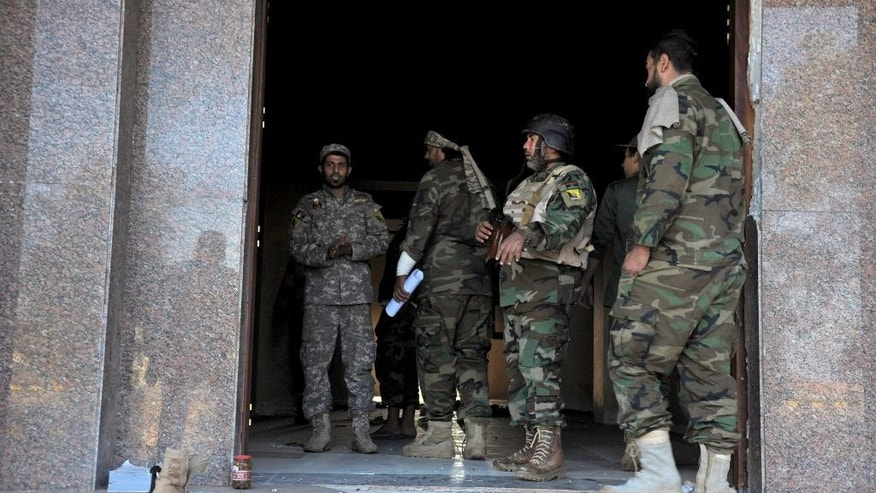 In this Monday, Nov. 3, 2014 photo, Libyan military soldiers stand at the entrance of a damaged empty building that was used by Islamic militias during heavy clashes in Benghazi, Libya. Clashes in Benghazi have killed at least 210 people since government troops backed by armed civilians started a campaign in mid-October to retake the city from Islamist militias. (AP Photo/Mohammed El-Sheikhy)