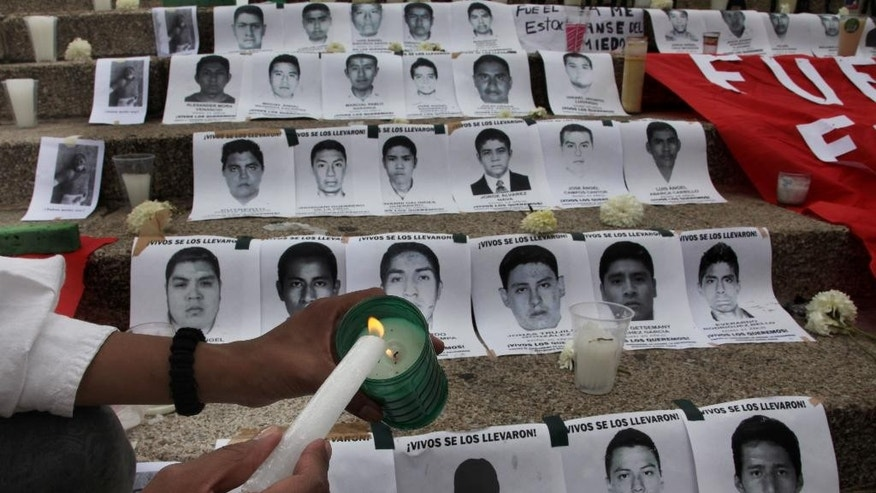 A woman lights a candle during a demonstration at the Angel of Independence, where the steps of the monument were lined with images of the 43 disappeared rural college students, in Mexico City, Saturday, Nov. 8, 2014. Suspects in the disappearance of 43 college students have confessed to loading the youths onto dump trucks, murdering them at a landfill, then burning the bodies and dumping the ashen remains into a river, Mexican authorities said Friday. (AP Photo/Marco Ugarte)