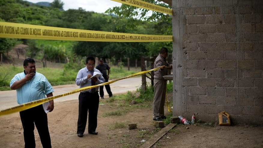 FILE - In this July 3, 2014 file photo, state authorities use crime scene tape to seal off an unfinished warehouse that was the site of a shootout between Mexican soldiers and alleged criminals on the outskirts of the village of San Pedro Limon in Mexico state, Mexico. The Federal Judiciary Council said Friday, Nov. 7, 2014 a Mexican judge ordered seven soldiers to stand trial in the killing of suspected gang members after they were subdued, the latest chapter in the government's tardy recognition that executions occurred at a grain warehouse in southern Mexico on June 30. The charges did little to resolve the mystery of how many of the 22 purported gang members killed that day after a gunbattle were executed by soldiers and how many soldiers were actually involved. (AP Photo/Rebecca Blackwell, File)
