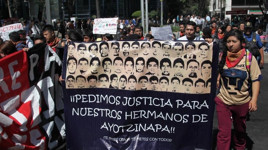 Students protest the disappearance of 43 students in the state of Guerrero, outside the general attorney's office in Mexico City, Thursday, Nov. 6, 2014. The 43 students have received far more attention than other disappeared, in part because allegedly corrupt police in Iguala so clearly played a role in their disappearance. Officers there are alleged to have worked for the Guerreros Unidos drug gang, which authorities charge had ties to the former mayor of Iguala, Jose Luis Abarca, and his wife, Maria de los Angeles Pineda. (AP Photo/Marco Ugarte)
