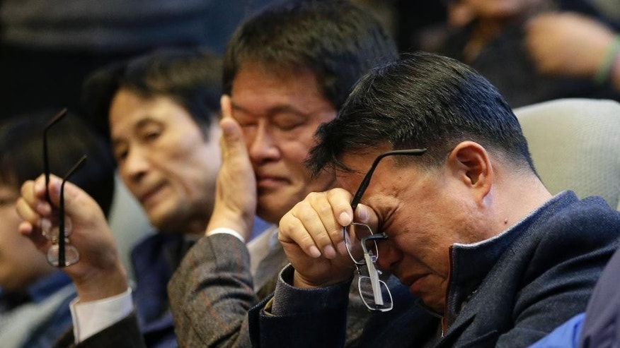 Family members of passengers aboard the sunken ferry Sewol wipe their tears after South Korean lawmakers voted during the plenary session at the National Assembly in Seoul, South Korea, Friday, Nov. 7, 2014. South Korea's National Assembly on Friday approved plans to disband the coast guard in the wake of criticism over its failure to rescue hundreds of passengers during the sinking of a ferry in April. (AP Photo/Lee Jin-man)