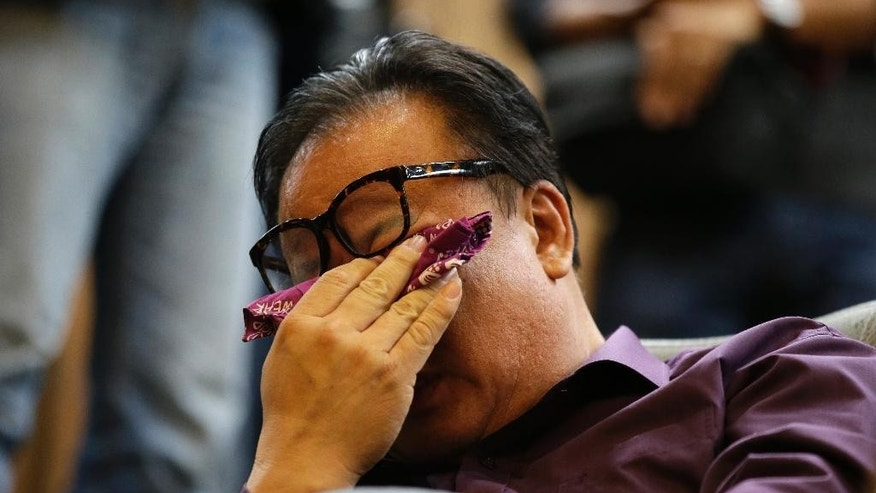 A family member of passengers aboard the sunken ferry Sewol 3wipes his tear during the plenary session at the National Assembly in Seoul, South Korea, Friday, Nov. 7, 2014. South Korea's National Assembly on Friday approved plans to disband the coast guard in the wake of criticism over its failure to rescue hundreds of passengers during the sinking of a ferry in April. (AP Photo/Lee Jin-man)