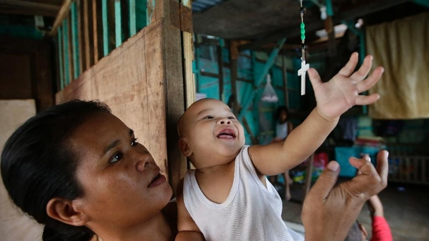 In this Thursday, Nov. 6, 2014 photo, typhoon survivor Agnes Bacsal, cuddles her youngest child John William, as he tries to reach a rosary hanging from the ceiling of their reconstructed home in Tacloban city, Leyte province, in central Philippines. Four months after she lost her husband and home to Typhoon Haiyan's fury, Agnes Bacsal gave birth to their sixth child  - a sprightly boy, whose company has eased the family's pain. (AP Photo/Bullit Marquez)