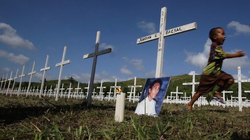 Typhoon survivor Jonathan Bacsal Jr., runs past a cross that indicates his father Jonathan Bacsal Sr. is buried at a mass grave for typhoon Haiyan victims in the outskirts of Tacloban city, Leyte province in central Philippines Thursday, Nov. 6, 2014.  His father perished after being hit by a flying piece of tin roof while trying to herd them to safety as the horrific Nov. 8, 2013 storm leveled entire villages in Tacloban city on Leyte island. The tsunami-like storm surges whipped by Haiyan swept away their house, plunging them into the rampaging floodwaters. (AP Photo/Bullit Marquez)