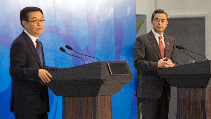 Chinese Commerce Minister Gao Hucheng speaks as Chinese Foreign Minister Wang Yi, right, listens during a press conference on the Asia-Pacific Economic Cooperation (APEC) related meetings at the China National Convention Center in Beijing, Saturday, Nov. 8, 2014. (AP Photo/Rolex Dela Pena, Pool)