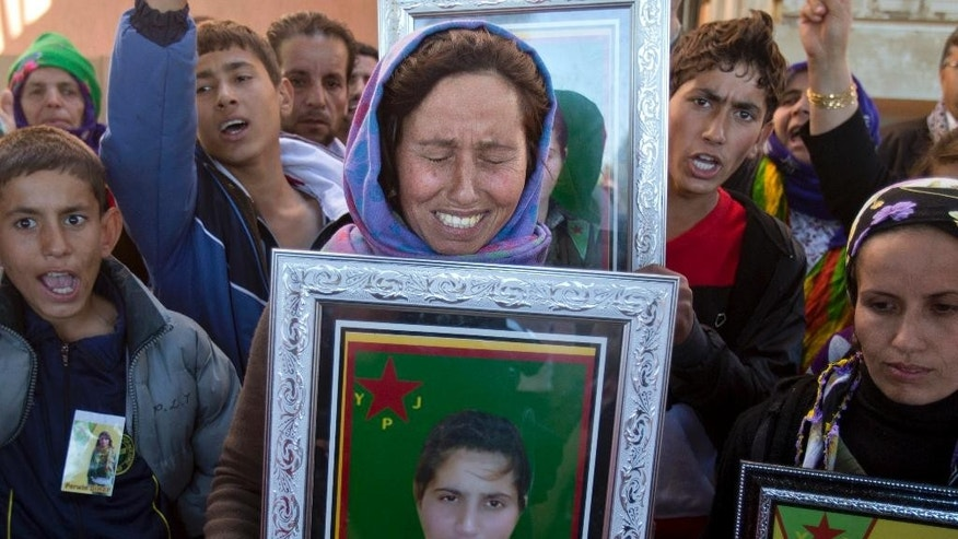 Jamila, center, sister of 19 year-old Syrian Kurdish fighter girl Perwin Mustafa Dihap who died after being wounded during fighting against the Islamic State forces in her home town of Kobani, cries holding her picture, during the funeral in Suruc, on the Turkey-Syria border Friday, Nov. 7, 2014. Kobani, also known as Ayn Arab, and its surrounding areas, has been under assault by extremists of the Islamic State group since mid-September and is being defended by Kurdish fighters. (AP Photo/Vadim Ghirda)
