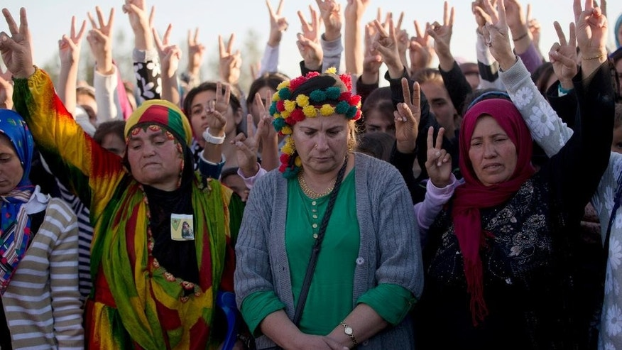 Mourners flash victory signs during the funeral of 19 year-old Syrian Kurdish female fighter Perwin Mustafa Dihap who died in Suruc, on the Turkey-Syria border Friday, Nov. 7, 2014, after being wounded during fighting against the Islamic State forces in her home town of Kobani. Kobani, also known as Ayn Arab, and its surrounding areas, has been under assault by extremists of the Islamic State group since mid-September and is being defended by Kurdish fighters. (AP Photo/Vadim Ghirda)