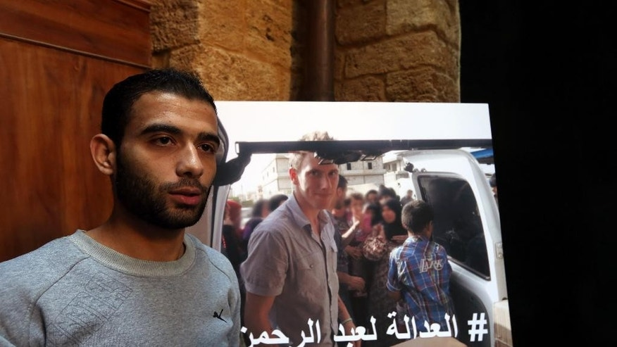 "Syrian refugee Amjad Moghrabi stands in front of a photograph of his colleague, American aid worker Peter Kassig, 26, who converted to Islam while in captivity and changed his name to Abdul-Rahman Kassig, during an interview with The Associated Press in the northern port city of Tripoli, Lebanon, Saturday, Nov. 8, 2014. Kassig was helping victims of the Syrian civil war when he was captured in Syria last year and threatened with beheading by the Islamic State group. Arabic  reads, ""Justice for Abdul-Rahman."" (AP Photo/Bilal Hussein)"
