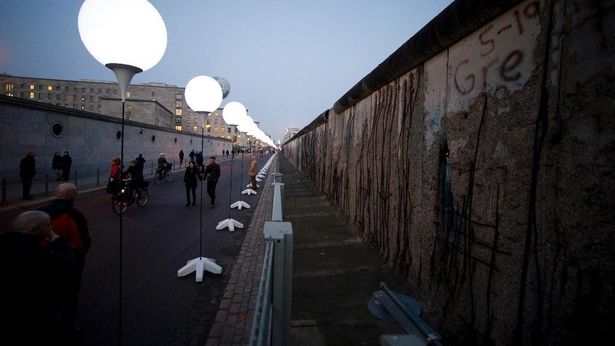 "People pass by balloons of the art project ""Lichtgrenze 2014"" or lightborder 2014, along the Berlin Wall in Berlin, Germany, Friday, Nov. 7, 2014. The light installation featuring 8,000 luminous white balloons commemorates the division of Berlin, marking the 25th anniversary of the fall of the wall on the weekend. (AP Photo/Steffi Loos)"