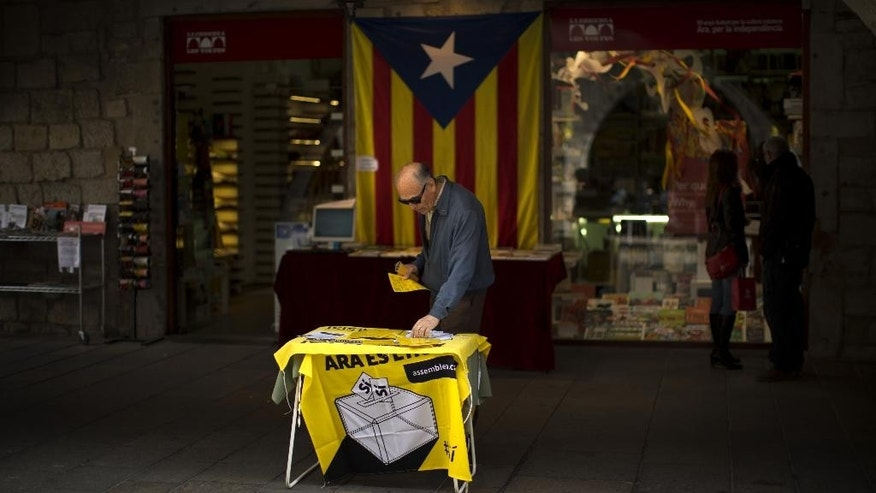 A man looks at information on a table about an informal poll scheduled for next Sunday in a street in Girona, Spain, on Saturday Nov. 8, 2014. The pro-independence regional government of Catalonia stages a symbolic poll on secession in a show of determination and defiance after the Constitutional Court suspended its plans to hold an official independence referendum following a legal challenge by the Spanish government. (AP Photo/Emilio Morenatti)