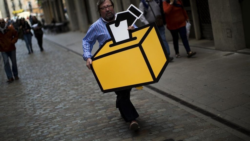 Businessman Emilio Busquets carries a drawing of a ballot box to decorate his shop ahead of voting on an informal poll, scheduled for next Sunday, in Girona, Spain, on Saturday Nov.8, 2014. The pro-independence regional government of Catalonia stages a symbolic poll on secession in a show of determination and defiance after the Constitutional Court suspended its plans to hold an official independence referendum following a legal challenge by the Spanish government. (AP Photo/Emilio Morenatti)