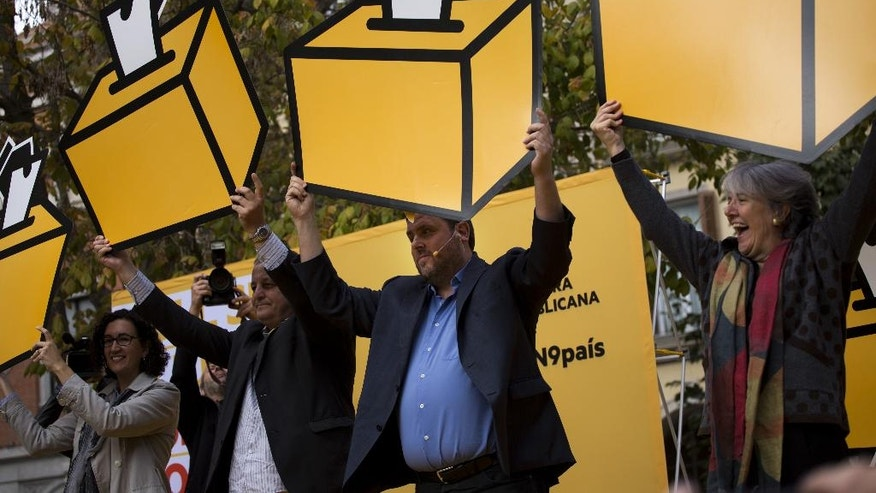 Oriol Junqueras, head of the pro-independence Republican Left of Catalonia, center, holds a drawing a of ballot box during a rally ahead of voting on an informal poll, scheduled for next Sunday, in Girona, Spain, on Saturday Nov.8, 2014. The pro-independence regional government of Catalonia stages a symbolic poll on secession in a show of determination and defiance after the Constitutional Court suspended its plans to hold an official independence referendum following a legal challenge by the Spanish government. (AP Photo/Emilio Morenatti)