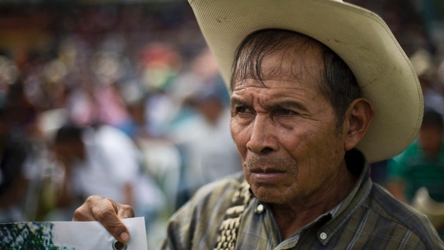 Andres Alvarado Sic, who was forced to abandon his home due to the construction of a hydroelectric dam, attends a meeting with Guatemalan President Otto Perez Molina in Rabinal, Guatemala, Saturday, Nov. 8, 2014. Perez Molina apologized to members of the surrounding Baja Verapaz communities for human rights violations committed against the Achi Indians, during the construction of the Chixoy Hydroelectric Dam, that began in 1975. (AP Photo/Moises Castillo)