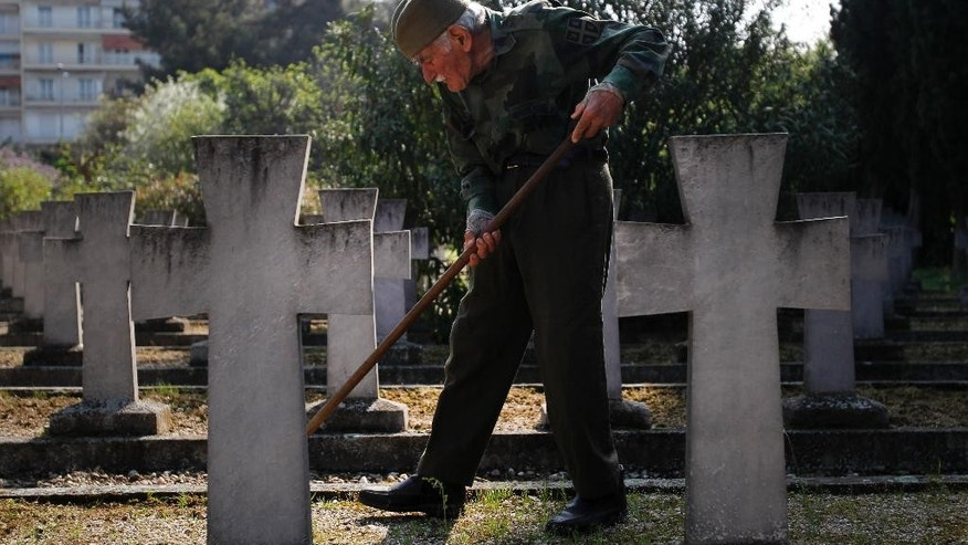 In this photo taken on Tuesday, April 8, 2014, cemetery keeper Djordje Mihailovic tends to graves at the Zeitenlik Allied War Cemetery in Thessaloniki, Greece. Following in the footsteps of his grandfather and father before him the 86-year old Mihailovic vows to stay for the rest of his days, tending to the graves of Serbia's casualties of World War I. Serbia, involved in the war from the very beginning, had an army of about 350,000 soldiers, of whom some 130,000 died, outnumbered as they fought off an Austro-Hungarian invasion for more than a year before Germany and neighbor Bulgaria joined the onslaught. (AP Photo/Nikolas Giakoumidis)