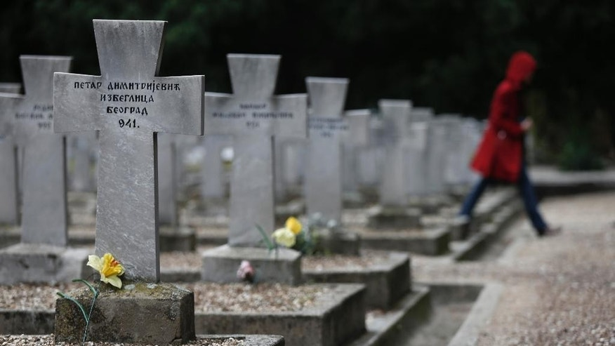 In this photo taken on Wednesday, Oct. 8, 2014, a woman walks through the rows of World War I graves at the Zeitenlik Allied War Cemetery in Thessaloniki, Greece. Serbia, where World War I started, suffered the heaviest losses among allied nations in relation to its population, outnumbered as it fought off an Austro-Hungarian invasion for more than a year until Germany and neighbor Bulgaria joined the offensive. (AP Photo/Petros Giannakouris)