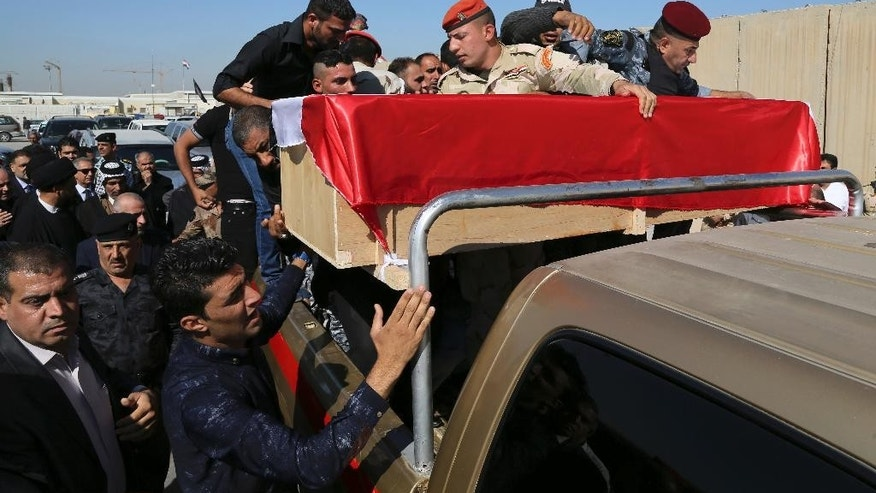 Mourners grieve as the body of police Lt. Gen. Faisal Malik is taken for burial before a funeral procession in Baghdad, Iraq, Saturday, Nov. 8, 2014. A suicide truck bomber targeting a senior police officer's convoy in Iraq late Friday killed several people, including the ranking official, authorities said Saturday. (AP Photo/Karim Kadim)