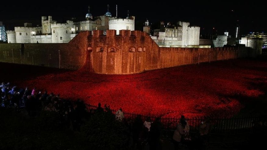 Members of the public stop Friday Nov. 7, 2014, to look at the ceramic poppies which form part of the art installation 'Blood Swept Lands and Seas of Red' by artist Paul Cummins at the Tower of London, marking the centenary of the First World War.  (AP Photo/PA, Jonathan Brady)  UNITED KINGDOM OUT  NO SALES  NO ARCHIVE
