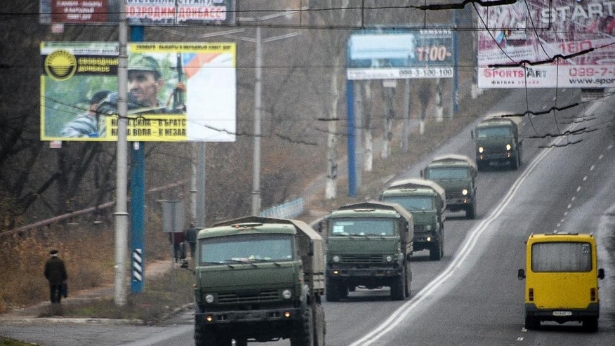Unmarked military vehicles travel along a road outside the separatist rebel-held town Makiivka, 25 km (16 miles) from Donetsk, eastern Ukraine on Saturday, Nov. 8, 2014. AP reporters saw more than 80 military vehicles on the move Saturday in separatist-controlled areas, indicating intensified hostilities may lie ahead. (AP Photo/Mstyslav Chernov)