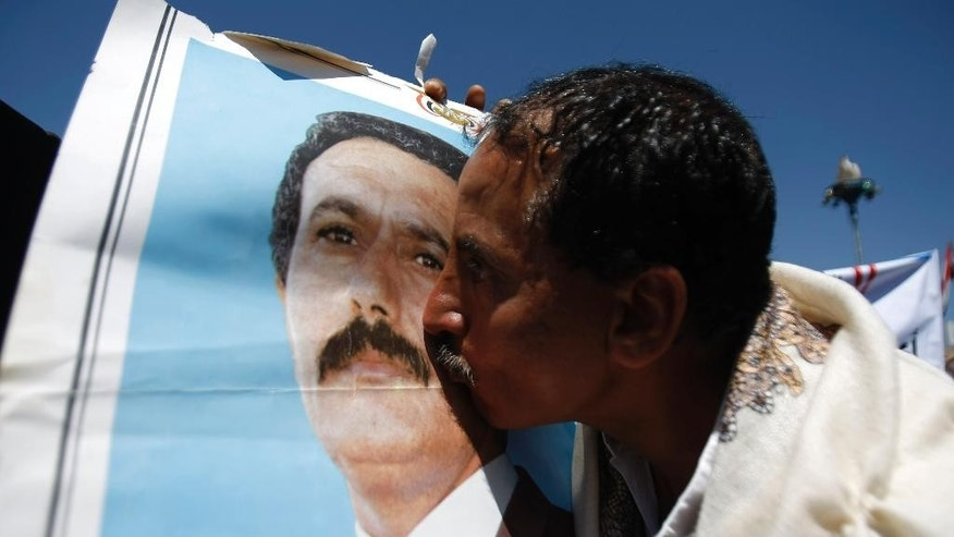 "A supporter of Yemen's ousted President Ali Abdullah Saleh kisses his picture during a demonstration against foreign interference in Sanaa, Yemen, Friday, Nov. 7, 2014. Thousands of supporters of Yemen's ousted president and Shiite rebels who have overrun the capital rallied in Sanaa, denouncing what they claim to be American ""interference"" in Yemen's affairs. (AP Photo/Hani Mohammed)"