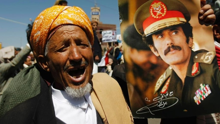 "A supporter of Yemen's ousted President Ali Abdullah Saleh, shown on a poster, chants slogans to express his rejection of U.S. Ambassador Matthew H. Tueller during a demonstration against foreign interference in Sanaa, Yemen, Friday, Nov. 7, 2014. Thousands of supporters of Yemen's ousted president and Shiite rebels who have overrun the capital rallied in Sanaa, denouncing what they claim to be American ""interference"" in Yemen's affairs. (AP Photo/Hani Mohammed)"