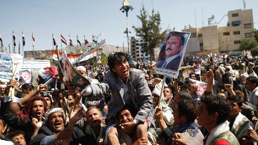 "Supporters of Yemen's ousted President Ali Abdullah Saleh, shown on a picture, center, chant slogans to express their rejection of U.S. Ambassador Matthew H. Tueller during a demonstration against foreign interference in Sanaa, Yemen, Friday, Nov. 7, 2014. Thousands of supporters of Yemen's ousted president and Shiite rebels who have overrun the capital rallied in Sanaa, denouncing what they claim to be American ""interference"" in Yemen's affairs. (AP Photo/Hani Mohammed)"