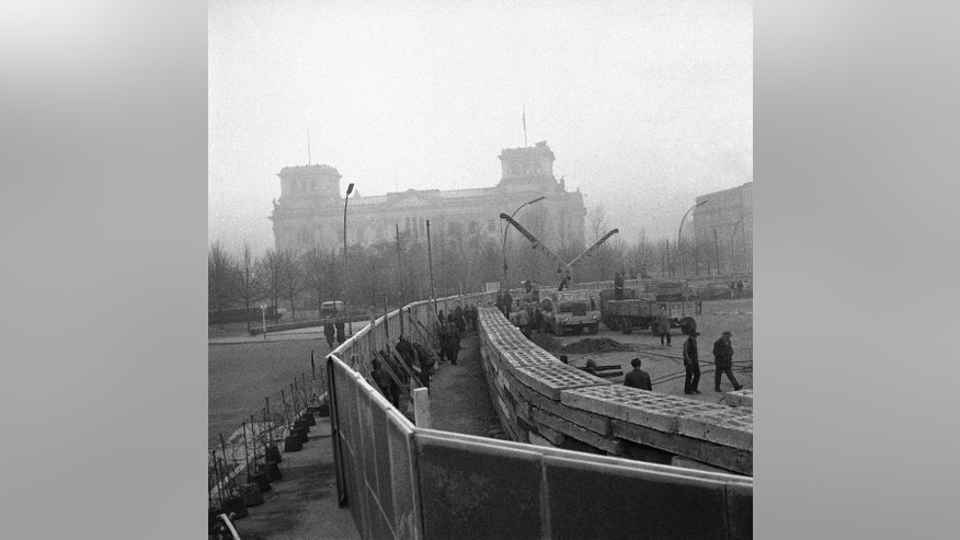 FILE - The Nov. 20, 1961 photo shows 12 feet high boards hiding the work as East German troops erect a new concrete wall at the Brandenburg Gate, marking the East-West border in Berlin. In background is the former Reichstag building which is in West Berlin.  (AP Photo/file)