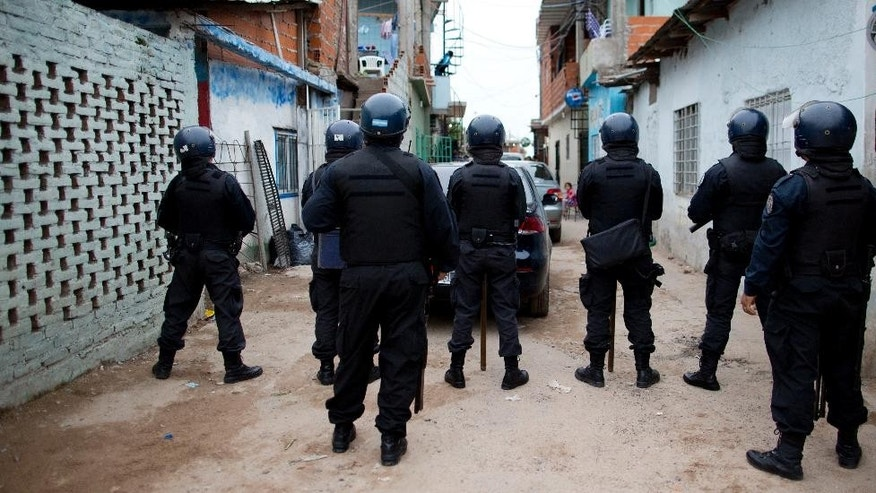 "In this April 11, 2014 photo, police officers stand at the ready during a drug raid  at the ""21"" slum in in Buenos Aires, Argentina. U.S.-led efforts to stifle the drug trade in more northern countries and in the Caribbean have pushed the traffic south to Argentina, according to drug experts and justice officials. (AP Photo/Natacha Pisarenko)"
