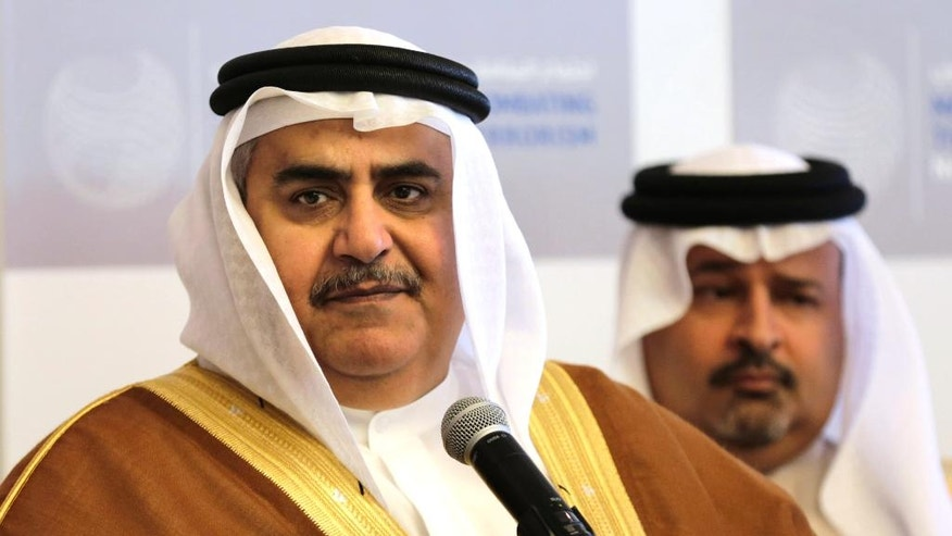 Bahraini Foreign Minister Sheik Khalid bin Ahmed Al Khalifa, left, listens to journalists while standing with Finance Minister Sheik Ahmed bin Mohammed Al Khalifa during a conference titled: Combating the Financing of Terrorism, in Manama, Bahrain, Sunday, Nov. 9, 2014. Representatives from several countries gathered to discuss ways to stop the flow of money to groups such as the extremist Islamic State group. (AP Photo/Hasan Jamali)