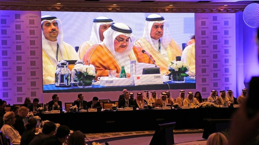 Bahraini Foreign Minister Sheik Khalid bin Ahmed Al Khalifa, center on screen, addresses delegates during a conference: Combating the Financing of Terrorism, in Manama, Bahrain, Sunday, Nov. 9, 2014. Representatives from several countries gathered to discuss ways to stop the flow of money to groups such as the extremist Islamic State group. (AP Photo/Hasan Jamali)